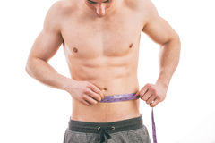 Male torso and blue tape measure. On white background Royalty Free Stock Photos