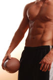 Male torso with football. Standing male with great abdomen on white holding football Royalty Free Stock Photography