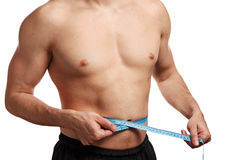 Male torso with measure tape on waistline Stock Photos
