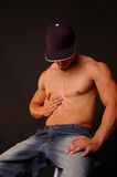 Male touch. Handsome male model wearing a ball cap and touching his abdomen Royalty Free Stock Images