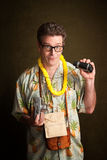 Male Tourist. In a tropical island outfit holding a camera and binoculars Royalty Free Stock Photography