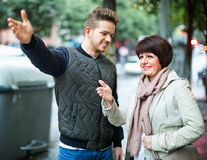 Male tourist asks for directions from   woman Stock Photography