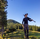 Male tourist on a background of mountains. A man with a tripod. royalty free stock photo