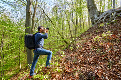 Male tourist with backpack in the forest. Professional photographer with backpack hiking in a beech forest Stock Photo