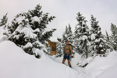 Male tourist with a backpack, with a naked torso and legs is amo. Ng the snowdrifts and trees Stock Images