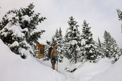 Male tourist with a backpack, with a naked torso and legs is amo. Ng the snowdrifts and trees Stock Photography