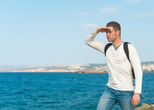 Male tourist with backpack. Male tourist with backpack standing near the sea Royalty Free Stock Image