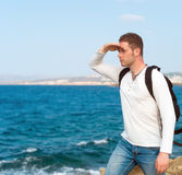 Male tourist with backpack. Male tourist with backpack standing near the sea Stock Photos
