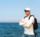 Male tourist. Male tourist with backpack standing near the sea Royalty Free Stock Photos