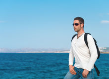 Male tourist. Male tourist with backpack standing near the sea Stock Photos