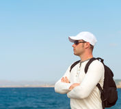 Male tourist. Male tourist with backpack standing near the sea Royalty Free Stock Images