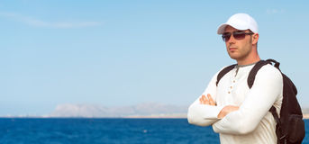Male tourist. Male tourist with backpack standing near the sea Stock Photography