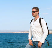 Male tourist. Male tourist with backpack standing near the sea Royalty Free Stock Image