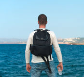 Male tourist with backpack. Male tourist with backpack standing near the sea. Place for your text Royalty Free Stock Images