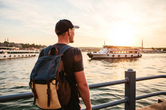 Male tourist with a backpack at sunset next to the Bosphorus in Istanbul. The concept of leisure, hiking, vacations. Male tourist with a backpack at sunset next Royalty Free Stock Image