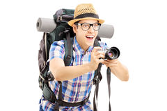Male tourist with backpack taking a picture with the camera. Isolated on white background Royalty Free Stock Photo