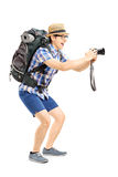 Male tourist with backpack taking a picture with his camera. Full length portrait of a male tourist with backpack taking a picture with his camera isolated on Royalty Free Stock Images