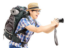 Male tourist with backpack taking a picture with his camera. Isolated on white background Royalty Free Stock Images