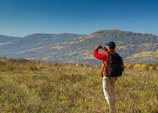 Male tourist with backpack taking pictures of  scenery to your s Royalty Free Stock Photos