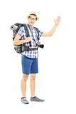 Male tourist with backpack waving with his hand. Full length portrait of a male tourist with backpack waving with his hand isolated on white background Stock Photo
