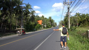 Male tourist backpacker hitch-hiking in Asia stock video