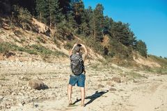 Male tourist backpacker photographing beautiful woodland landscape. Hot day in taiga royalty free stock photo