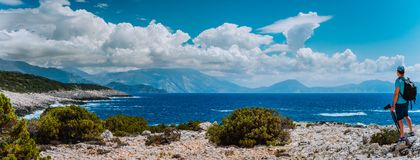 Male tourist with camera admiring breathtaking cloud scenery over the mountain range at the Mediterranean sea coast. Sunning outdoor scene of Ionian Islands Royalty Free Stock Images