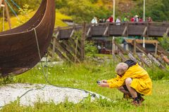 Man taking photo from old viking boat in norway. Male tourist with camera taking photo of old wooden viking boat on seashore in norwegian nature. Mountains and Stock Photos