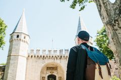 Tourist in casual clothes with backpack admires the Topkapi Palace in Istanbul Stock Photography
