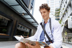 Male tourist in city. Happy male tourist in city with camera and map Stock Photography