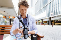 Male tourist in city. Happy male tourist in city with camera and map Stock Photos