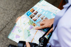 Male tourist in city. Happy male tourist in city with camera and map Royalty Free Stock Photography
