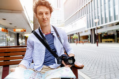 Male tourist in city. Happy male tourist in city with camera and map Stock Images