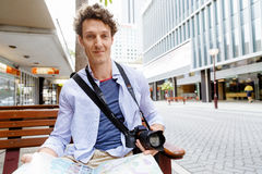 Male tourist in city. Happy male tourist in city with camera and map Stock Photo