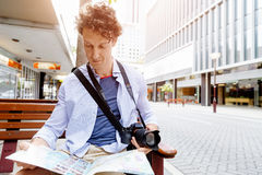 Male tourist in city. Happy male tourist in city with camera and map Royalty Free Stock Images