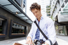 Male tourist in city. Happy male tourist in city with camera and map Stock Image