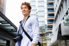 Male tourist in city. Happy male tourist in casual clothes in city with camera Stock Photography