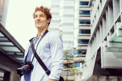 Male tourist in city. Happy male tourist in casual clothes in city with camera Stock Photo