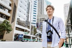 Male tourist in city. Happy male tourist in casual clothes in city walking Stock Photography