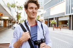 Male tourist in city. Happy male tourist in casual clothes in city walking Stock Images