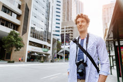 Male tourist in city. Happy male tourist in casual clothes in city walking Royalty Free Stock Image