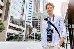 Male tourist in city. Happy male tourist in casual clothes in city walking Stock Photo