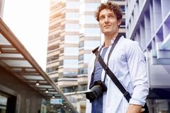 Male tourist in city. Happy male tourist in casual clothes in city with camera Royalty Free Stock Images