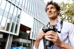 Male tourist in city. Happy male tourist in casual clothes in city walking Royalty Free Stock Photo