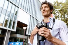 Male tourist in city. Happy male tourist in casual clothes in city walking Stock Image