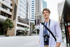 Male tourist in city. Happy male tourist in casual clothes in city walking Stock Photos
