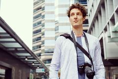 Male tourist in city. Happy male tourist in city walking with camera Royalty Free Stock Photo