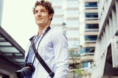 Male tourist in city. Happy male tourist in city walking with camera Stock Photography