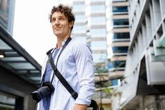 Male tourist in city. Happy male tourist in city walking with camera Royalty Free Stock Image