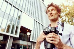Male tourist in city. Happy male tourist walking in city with camera Royalty Free Stock Photography